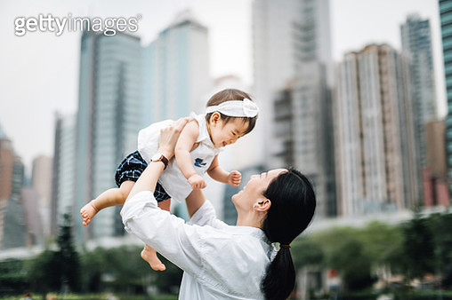 Joyful mother and cute baby girl having happy family time as mother lifting baby girl up in the air in urban park against highrise city buildings - gettyimageskorea