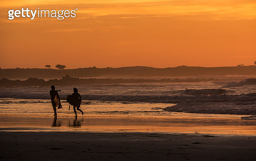 Surfers on the Beach at Sunset - gettyimageskorea