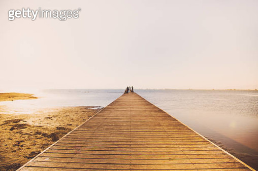 Beautiful minimal landscape with wood pier over the Mediterranean Sea in the Ebro Delta during sunset light with people in a beautiful tranquility pic. - gettyimageskorea