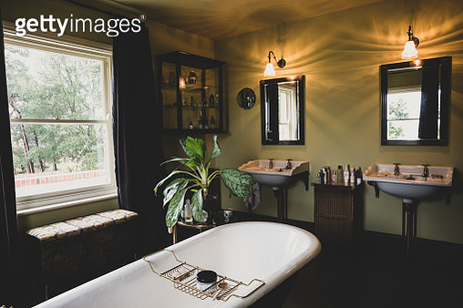 Interior view of bathroom with black mirrors over two Victorian wash stands, sash window and roll top bath with brass bath caddy. - gettyimageskorea