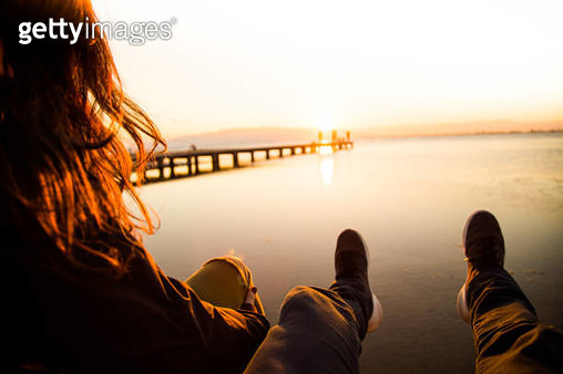 Beautiful couple in love sitting and contemplating the sunset over the Ebro Delta in the Mediterranean sea from wood pier and stunning sunlight during a weekend travel in the region. - gettyimageskorea