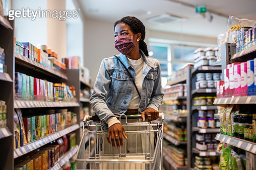 Female customer with face mask shopping at a grocery store - gettyimageskorea