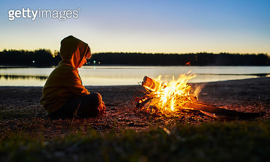 Argentina, Patagonia, Concordia, boy sitting at camp fire at a lake - gettyimageskorea
