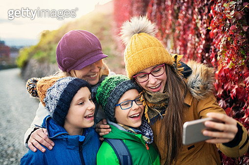 Mother with three kids sightseeing city of Brno. Family is taking selfies near the city walls covered in colorful ivy. Sunny autumn day.Nikon D850 - gettyimageskorea