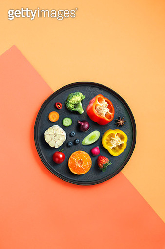 Minimalist style healthy eating colourful sliced vegan food in black plate on coloured background. - gettyimageskorea