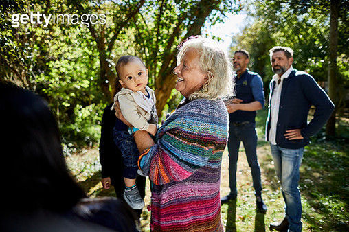 Grandmother holding grandson on a garden party - gettyimageskorea