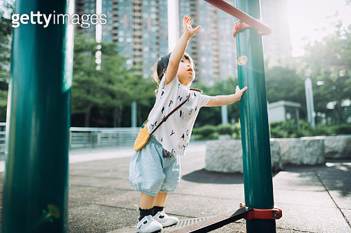 Playful little toddler girl arms raised and trying to reach a pull up bar at the outdoor playground on a lovely sunny day - gettyimageskorea