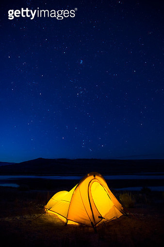Starry sky over illuminated tent at Soda Lake, Pinedale, Sublette County, Wyoming, USA - gettyimageskorea