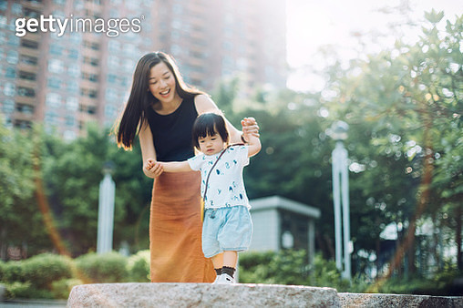 Joyful young Asian mother holding hands of little daughter supporting and assisting her walking along on stone on a lovely sunny day - gettyimageskorea
