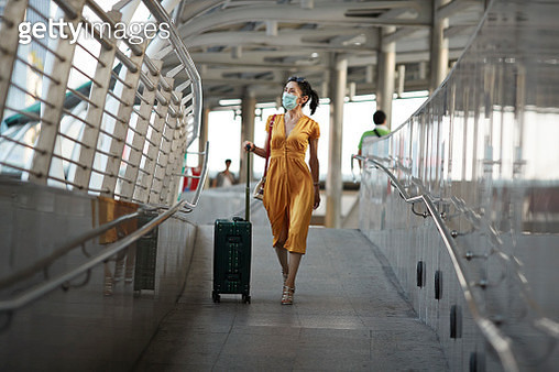 Full length of woman walking with luggage at railroad station - gettyimageskorea