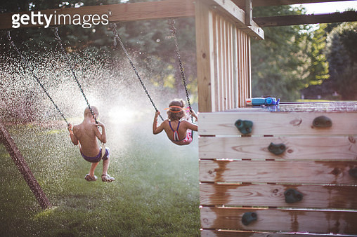 Children Swinging Into a Sprinkler - gettyimageskorea