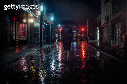 Streetlights shining in the reflections on the wet, empty and rainy street, woman walking, holding up an umbrella. Cinematic image in urban surroundings. - gettyimageskorea