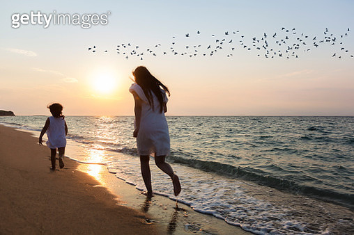 Young mother with her little daughter running on the beach - gettyimageskorea