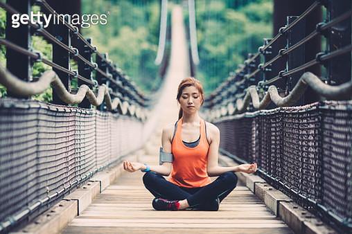 Sportswoman practicing yoga at the rope bridge - gettyimageskorea