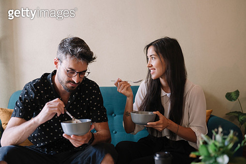 Young couple siiting on a couch in a cafe having breakfast - gettyimageskorea