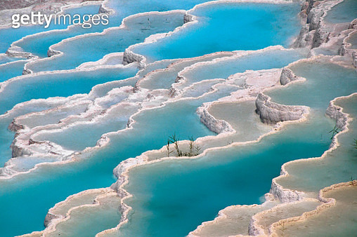 View of travertine terrace formations, deposited by water from the hot springs, in Pamukkale, a UNESCO World Heritage Site in Denizli province, Aegean region of Turkey. - gettyimageskorea