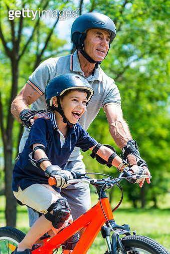 Grandfather Teaching Grandson To Ride Bicycle At Park - gettyimageskorea