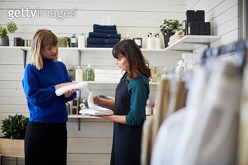 Female owner assisting customer in choosing textile at store - gettyimageskorea