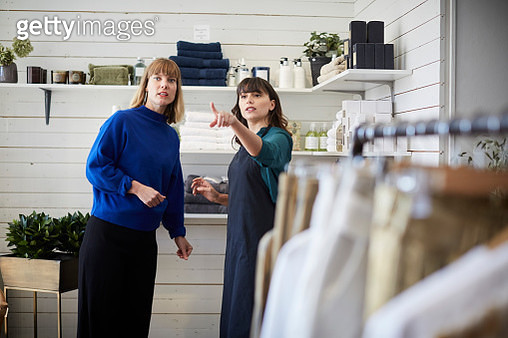 Female owner pointing and showing while communicating with customer at boutique - gettyimageskorea