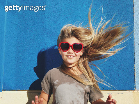 Portrait of a young girl with hair blowing in strong winds - gettyimageskorea