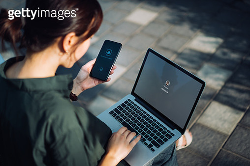 Young Asian businesswoman sitting on the bench in an urban park working outdoors, logging in to her laptop and holding smartphone on hand with a security key lock icon on the screen. Privacy protection, internet and mobile security concept - gettyimageskorea