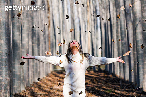 Young Woman With Arms Outstretched Standing In Forest During Autumn - gettyimageskorea