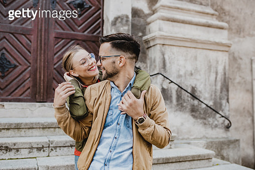 Portrait of a young couple on the street together, they are standing on the stairs ond hugging - gettyimageskorea