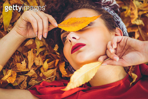 Young beautiful caucasian woman lying on autumn leaves. - gettyimageskorea