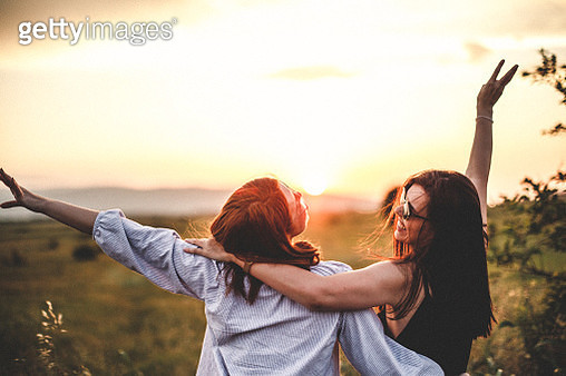Teen girls look at the sunset - gettyimageskorea