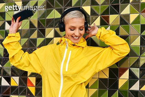 Cropped shot of an attractive young woman standing against a wall and listening to music from her cellphone through headphones - gettyimageskorea