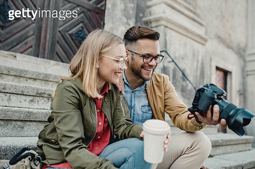 Portrait of a young couple on the street together, they are sitting on the stairs and looking pictures on the camera - gettyimageskorea
