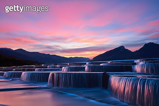 Side view of stepped waterfall group at sunrise in pink sky. - gettyimageskorea