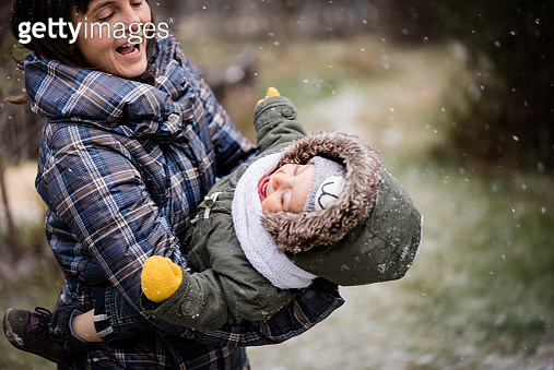 Mother playing outdoors with child during snowfall - gettyimageskorea