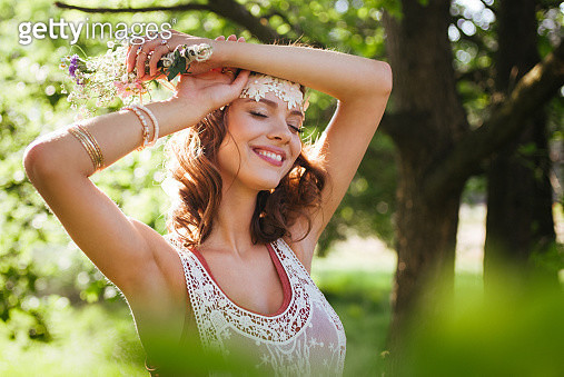 Serene boho girl looking relaxed in a summer park - gettyimageskorea