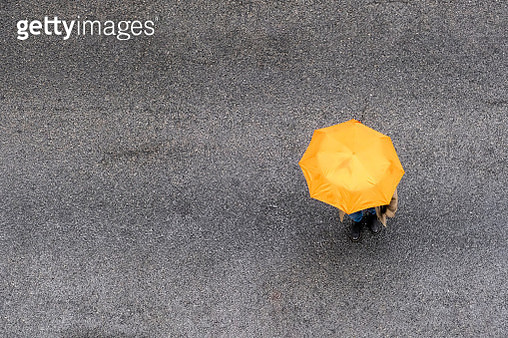 Aerial view of person with orange umbrella on street. - gettyimageskorea