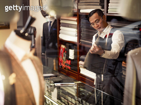 Tailor looking at fabric in traditional tailors shop - gettyimageskorea