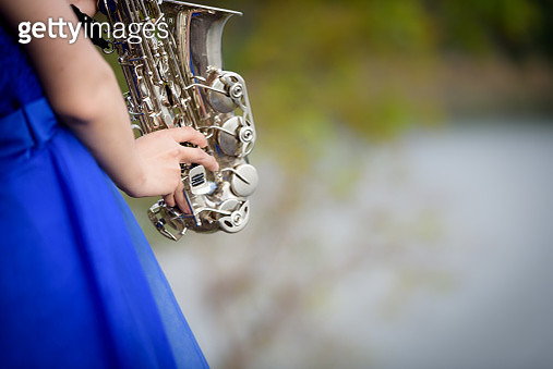 Midsection Of Young Bride Playing Saxophone In Park - gettyimageskorea