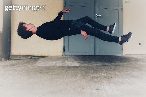 Side View Of Young Man Levitating At Home - gettyimageskorea