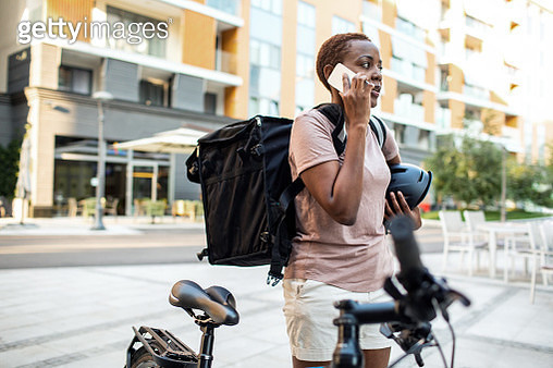 African delivery woman delivering package to customer. Talking on mobile phone. - gettyimageskorea