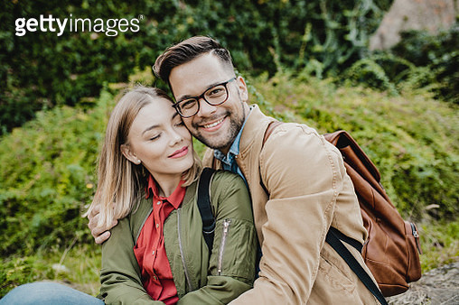 Portrait of young couple sitting on the wall in the park - gettyimageskorea