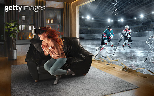 Beautiful woman at home on a black sofa with VR headset emotionally playing in virtual reality Hockey - gettyimageskorea