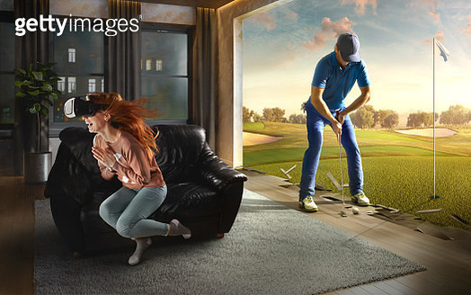 Beautiful woman at home on a black sofa with VR headset emotionally playing in virtual reality Golf - gettyimageskorea
