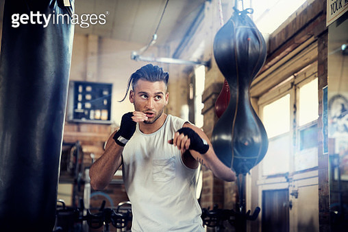 Hispanic man punching speed bag in gymnasium - gettyimageskorea