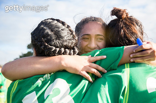 Three female sports players embrace - gettyimageskorea