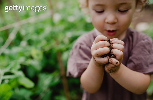 A little toddler in the garden, playing. Copy space. - gettyimageskorea