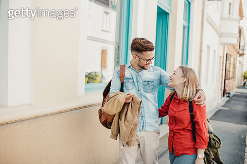 Portrait of a young couple on the street together. They are walking and smiling - gettyimageskorea