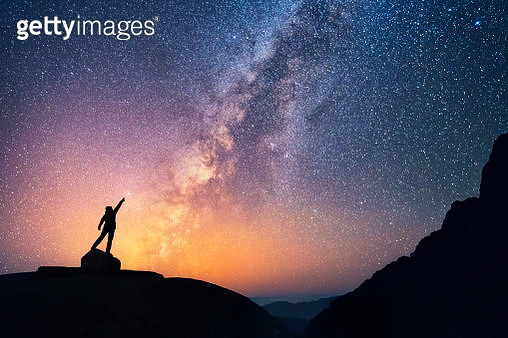 A person is standing next to the Milky Way galaxy pointing on a bright star. - gettyimageskorea