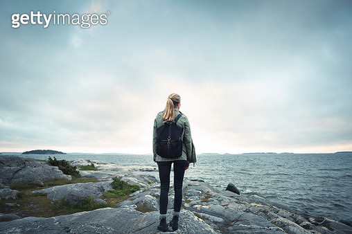 Rear view of woman standing on rock by sea against cloudy sky - gettyimageskorea