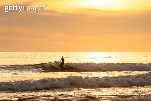 Surfer enjoys last waves of the day - gettyimageskorea