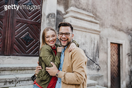 Portrait of young couple on the street together, looking at camera and smiling - gettyimageskorea